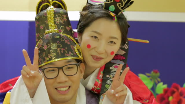 Korean traditional groom carrying bride on his back and the bride showing v sign to camera (Korean post wedding custom called Pyebaek)