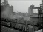 Krupp steel factory w/ smokestacks smoking Railroad coal cars in factory yard Worker pushing ladle of molten metal workers helping pour hot metal...