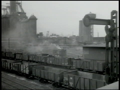 Krupp steel factory w/ smokestacks smoking Railroad coal cars in factory yard Worker pushing ladle of molten metal workers helping pour hot metal...