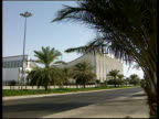 Kuwait National Assembly building zoom to side of building near roads and palm trees