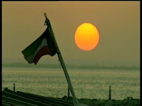 Kuwaiti flag blowing in breeze sea and glowing orange sun in background Kuwait
