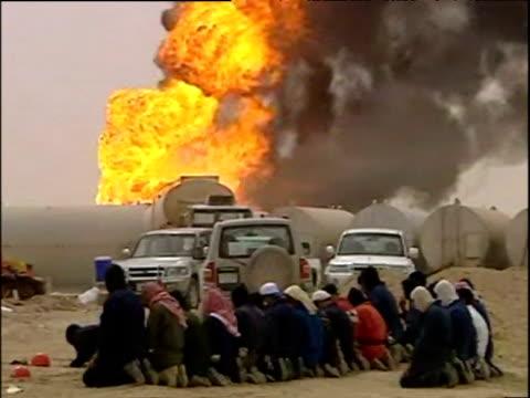 Kuwaiti Muslims pray near raging oil well fire Kuwait 2003