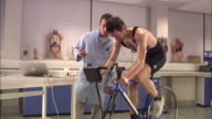 WS, Laboratory worker supervising man riding stationary bicycle, London, England