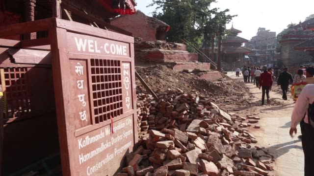 WS Laborers demolish a destroyed building WS Pedestrians walk past tents at an internal displacement camp at Durbar Square in Lalitpur Kathmandu...