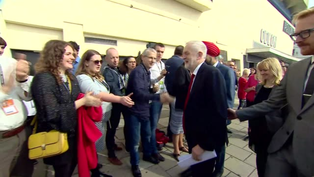 Jeremy Corbyn arrival ENGLAND East Sussex Brighton EXT People queuing outside conference venue / Jeremy Corbyn MP and Tan Dhesi MP arriving to cheers...