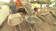 labourer dumps wheelbarrow load of concrete onto driveway being constructed and returns to truck concrete down shute and into barrow / close up...