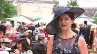 'Ladies' Day' at Royal Ascot Reporter to camera Woman wearing pink hat with feathers posing Woman wearing white and black hat posing Young girl...