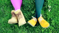 Ladies' feet in vivid shoes against green grass
