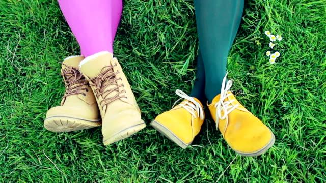 Ladies voeten in levendige schoenen tegen groen gras