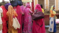 Ladies with colourful saris outside a Temple at Pushkar Mela Fair it comes alive with vibrant folk music and dances horse and camel races religious...