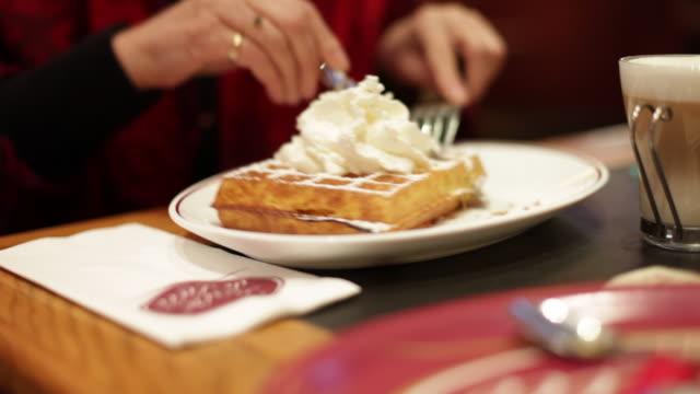 Lady eating waffle in cafe in Antwerp Belgium