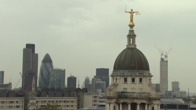 Lady Justice statue on top of Old Bailey with city of London in background