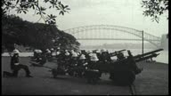 Lady Macquarie's Chair Soldiers in dress uniform run to a line up of canons for 21 gun salute and fire them Sydney Harbor Bridge in the back ground