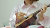 Lady playing Ukulele .Front view. From right to left.