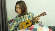 Lady playing Ukulele .Front view. From top to bottom.