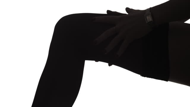 Lady Puts on Stockings Lingerie in Silhouette Close up