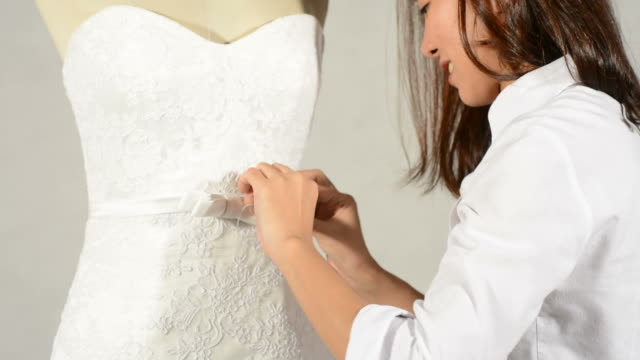 Lady sewing bride gown