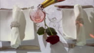 A laid table with a red rose.