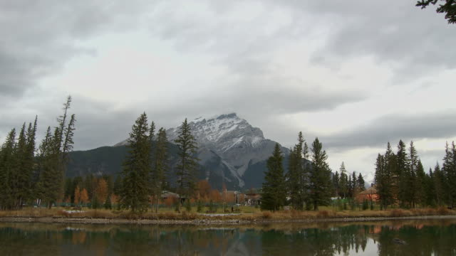 WS Lake and snow capped Cascade Mountain, jogger in distance / Banff, Alberta, Canada