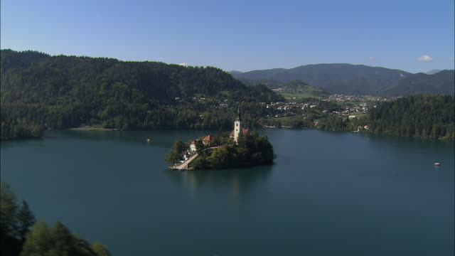 LOW AERIAL Lake Bled with Pilgrimage Church of the Assumption of Mary on small island / Slovenia