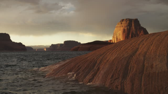 WS Lake Powell waves splashing against rocky coast at sunset / Utah, USA