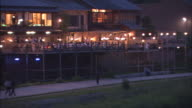 Lampposts illuminate the deck of a restaurant on the bank of the Kamogawa River.