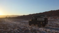 Land Rover Defender driving towards the sunset in the Valle De La Luna salt desert