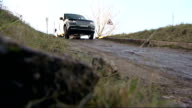 Land Rover prospering against the odds EXT Land Rover car along through deep muddy water / Car over tipping plate as being tested / Car over hill and...