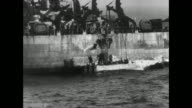 Landing barges carrying soldiers heading towards shore / soldier on beach signaling as barges approach / VS soldiers wading through water towards...