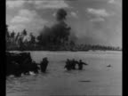 WS US landing barges in ocean with ship behind during invasion of Tarawa in World War II / landing barges move forward / montage Marines wade to...