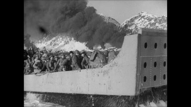 VS Landing craft boat filled w/ British Norwegian soldiers Norwegian refugees at sea burning coastline BG LA WS British Navy flag on ship smoke stack...
