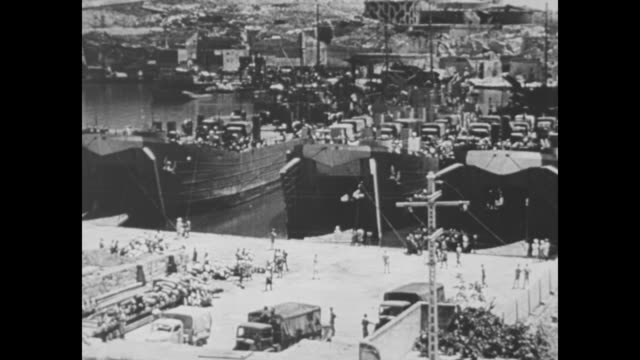 VS landing crafts barges and boat in water / barges move toward landing ship tank as soldiers watch from deck / wipe / VS troop ships and troops at...