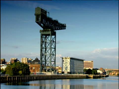 Landmark buildings in Glasgow set against a bright blue sky.