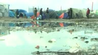 Landmark court ruling could mean hundreds of young refugees in Calais jungle camp are allowed into Britain T12111542 / TX Men along by tents and...
