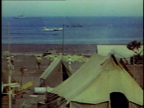 B29 lands in the water next to a camp on the beach / Iwo Jima Japan