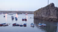 4K | Landscape of sea fishing port at dusk. In this wide angle shot we see colorful fishing boats and a big rock. The yellow light of the lamps mixes with blue sea and sky. Seagulls cross the frame flying away.
