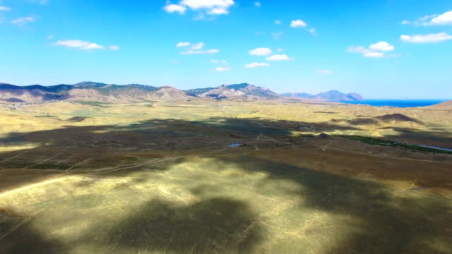 AERIAL: Landscape of steppes and hills on blue sky background