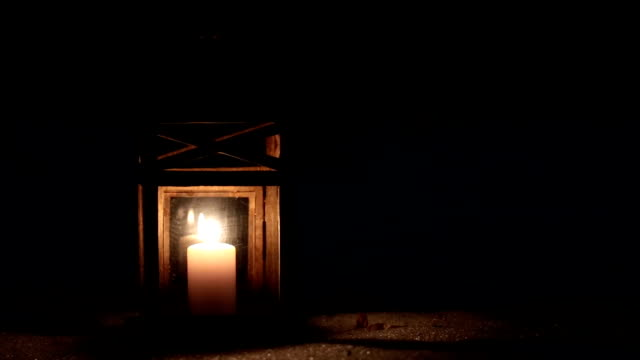 Lantern with a candle in the winter forest at night.