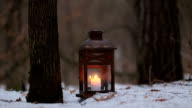 Lantern with a candle in the winter forest.