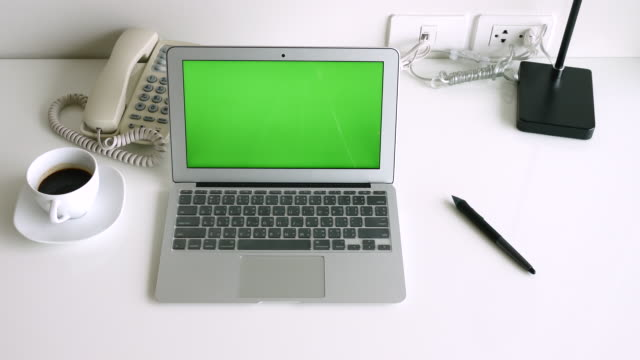 Laptop with green screen in modern office