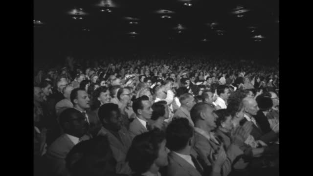 VS large audience in semidarkness listening and applauding Democratic presidential candidate Adlai Stevenson with numerous motion picture cameras on...