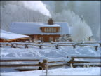 Large cabin in snow with smoke coming from chimney