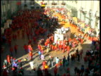 WS HA Large crowd and people in horse carriage throwing oranges at each other during Battle of Oranges on city square / Ivrea, Torino, Italy / AUDIO