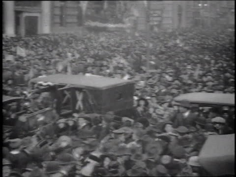 Large crowd in streets cheering the end of WWI and waving American flags / United States