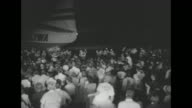 Large crowd mills around the tail of a TWA airplane / Dean Martin and Jerry Lewis are welcomed with handshakes at the base of boarding stairs / Lewis...