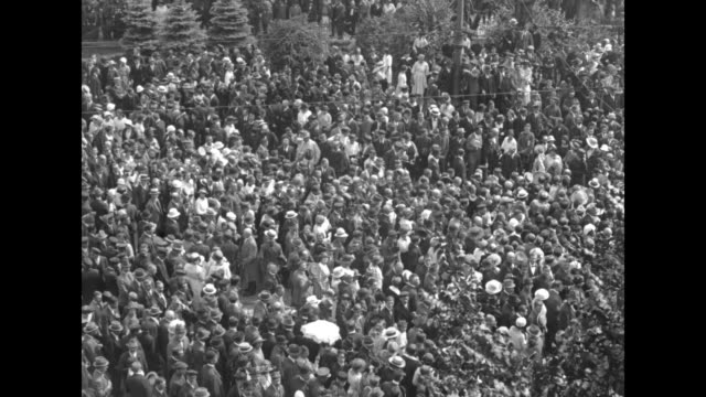 VS large crowd of people walk in Warsaw street carrying banners / political activist Wojciech Korfanty acknowledges people from balcony / unruly...