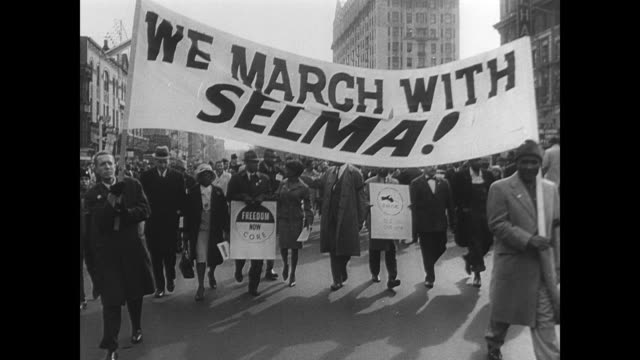 Large crowd of protestors walking from Selma to Montgomery to request equal voting rights for African Americans / CU banner 'WE MARCH WITH SELMA' /...