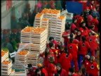 WS ZO HA Large crowd standing by stacks of crates filled with oranges during Battle of Oranges on city square / Ivrea, Torino, Italy / AUDIO