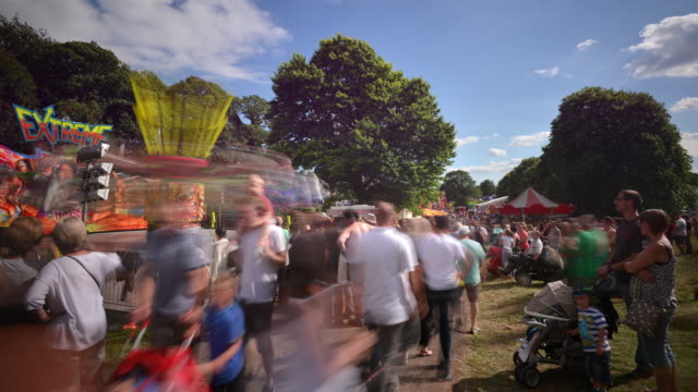 Large crowds at the Bristol international Balloon Fiesta rapidly pass through the frame some stop to enjoy the carnival rides