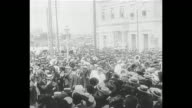Large crowds surround people marching down street with banners followed by Allied officers / troops marching on parade ground / pan of Greek Orthodox...